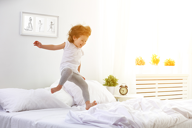 Toddler girl jumping on bed