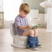 Little boy reading a book on the potty