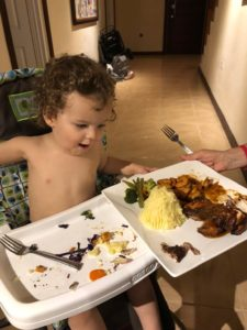 Happy baby looking at an adult sized meal